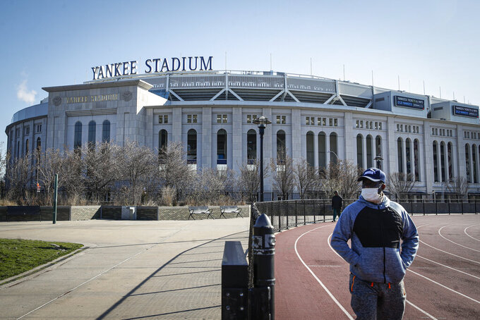 Un individuo con un mascarilla hace ejercicio camina cerca del Yankee Stadium, el jueves 26 de marzo de 2020. (AP Foto/John Minchillo)