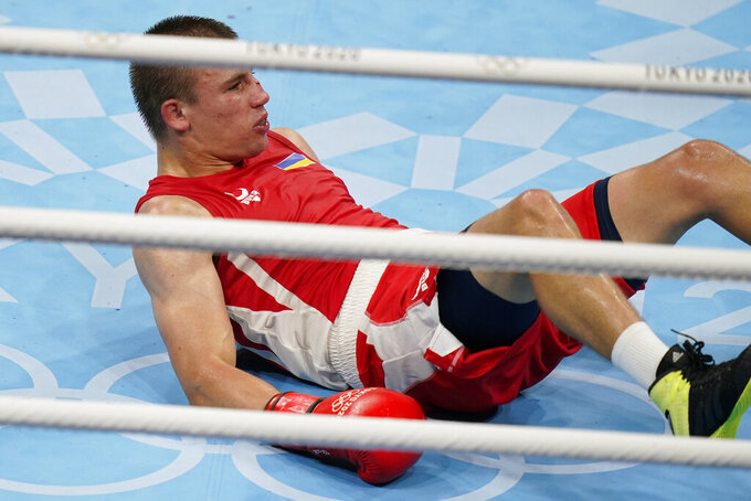 Ukraine's Oleksandr Khyzhniak, hits the mat after a punch from Brazil's Hebert Sousa during their men's middleweight 75-kg boxing gold medal match at the 2020 Summer Olympics, Saturday, Aug. 7, 2021, in Tokyo, Japan. (AP Photo/Frank Franklin II)