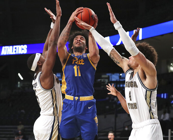 Georgia Tech's Moses Wright, left, and Jordan Usher, right, double team Pittsburgh forward Justin Champagnie, center,  during an NCAA college basketball game on Sunday, Feb. 14, 2021, in Atlanta. Georgia Tech beat Pittsburgh 71-65. (Curtis Compton/Atlanta Journal-Constitution via AP)