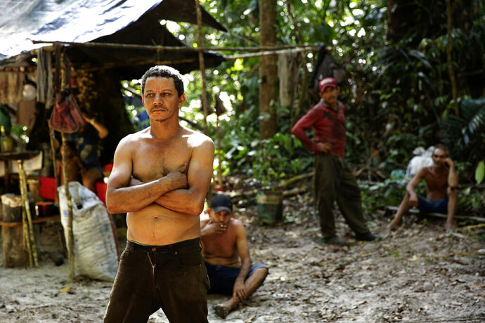 Zeca Pilao, leader of an illegal logger camp, talks with Tenetehara Indigenous men from the Ka'Azar, or Forest Owners, who discovered the encampment while patrolling their lands on the Alto Rio Guama reserve in Para state, near the city of Paragominas, Brazil, Tuesday, Sept. 8, 2020. Three Tenetehara Indigenous villages are patrolling to guard against illegal logging, gold mining, ranching, and farming as increasing encroachment and lax government enforcement during COVID-19 have forced the tribe to take matters into their own hands. (AP Photo/Eraldo Peres)