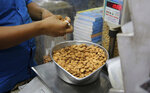 In this Saturday, June 22, 2019 photo, a shopkeeper weighs California almonds for a customer at a shop in New Delhi, India. California almond farmers are facing long-term uncertainty in the wake of new tariffs on exports to India, the state's top market for almonds. Farmers and experts predict the tariffs, leveled by India amid trade tensions with the United States, will complicate almond sales abroad. The tariffs may result in increased almond prices for buyers, so farmers expect to sell less. (AP Photo/Altaf Qadri)