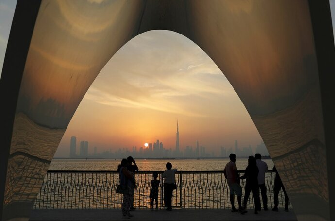 FILE- In this Friday, Oct. 18, 2019 file photo, people enjoy a city skyline view with the World's tallest building Burj Khalifa, in Dubai, United Arab Emirates.  In an unmarked villa, nestled amid homes in an upscale Dubai neighborhood, sits the first fully functioning synagogue in the Arabian Peninsula in decades.  Though its members keep its precise location secret, the synagogue's existence and the tacit approval it has received from this Islamic sheikhdom represents a slow rebirth of a burgeoning Jewish community in the Persian Gulf uprooted over the decades after the creation of Israel.   (AP Photo/Kamran Jebreili, File)