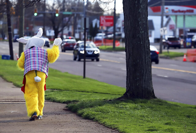 Maureen Salley, of Forty Fort, Pa., waves to motorists as she walks along Wyoming Avenue in Forty Fort, Pa., dressed like the Easter Bunny, Wednesday, April 8, 2020. With Easter approaching during the coronavirus pandemic where most of the country is under some form of lockdown, Salley said,