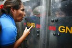 An opposition protester talks to soldiers of the National Guard blocking the way to the headquarters of the electricity State company in Caracas, Venezuela, Thursday, Oct. 24, 2019. Demonstrators mobilized in support of the inhabitants of the western state of Zulia, which suffers daily power outages that sometimes last more than 20 hours. (AP Photo/Ariana Cubillos)