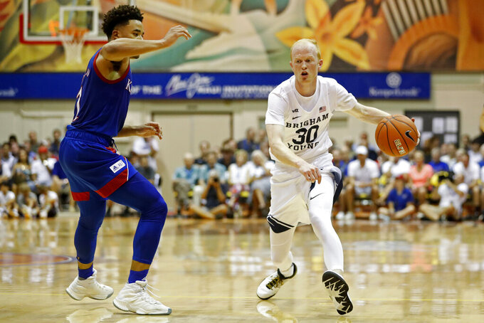 BYU guard TJ Haws (30) tries to get around Kansas guard Devon Dotson (1) during the first half of an NCAA college basketball game, Tuesday, Nov. 26, 2019, in Lahaina, Hawaii. (AP Photo/Marco Garcia)