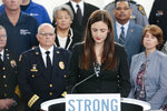 Whitney Austin, a survivor of the September 2018 mass shooting at the Fifth Third Center in Cincinnati, becomes emotional while recounting her experience during a news conference Monday, Oct. 7, 2019 at the Ohio Department of Public Safety in Columbus, Ohio. Republican Gov. Mike DeWine's new proposals to address Ohio gun violence in the wake of the Dayton mass shooting don't include background-check requirements for gun sales or a so-called red-flag law to restrict firearms for people perceived as threats, despite his earlier support of those ideas. Instead, his administration detailed legislative proposals Monday intended to increase and improve background checks and ensure people don't have firearms if a court has deemed them to be a danger. (Joshua A. Bickel/The Columbus Dispatch via AP)