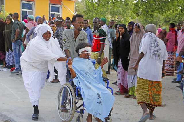 A civilian who was wounded in suicide car bomb attack is helped to be taken to hospital in Mogadishu, Somalia, Saturday, Dec, 28, 2019. A police officer says a car bomb has detonated at a security checkpoint during the morning rush hour in Somalia's capital. (AP Photo/Farah Abdi Warsame)