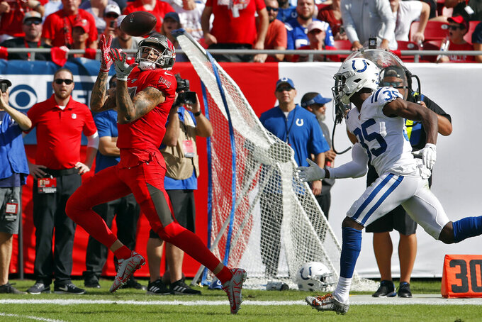 Tampa Bay Buccaneers wide receiver Mike Evans (13) pulls in a 61-yard touchdown reception in front of Indianapolis Colts cornerback Pierre Desir (35) during the first half of an NFL football game Sunday, Dec. 8, 2019, in Tampa, Fla. (AP Photo/Mark LoMoglio)