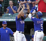 Texas Rangers' Rougned Odor, center, congratulates Willie Calhoun for his home run during the second inning of the team's baseball game against the Los Angeles Angels on Wednesday, Aug. 21, 2019, in Arlington, Texas. (AP Photo/Louis DeLuca)