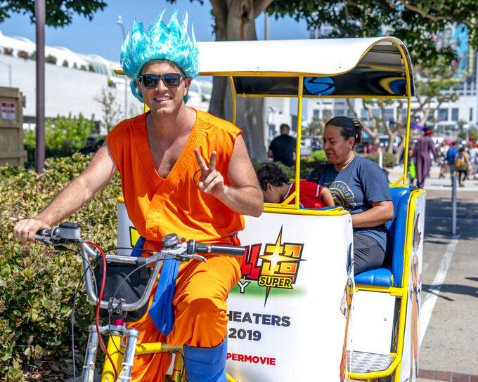 "FILE - In this July 20, 2018 file photo, a pedicab driver dressed as a character from the anime franchise ""Dragon Ball"" gestures as he carries passengers during Comic-Con International in San Diego. ""Dragon Ball"" is a revered anime that has influenced pop culture for years, earning praise from the likes of Michael B. Jordan, Ronda Rousey and Chris Brown, showing up in end zone celebrations and even at the Macy's Thanksgiving Day Parade. With the new film ""Dragon Ball Super: Broly"" releasing this week in the U.S., the franchise's popularity with its famous and non-famous fans is likely to grow. (Photo by Christy Radecic/Invision/AP, File)"
