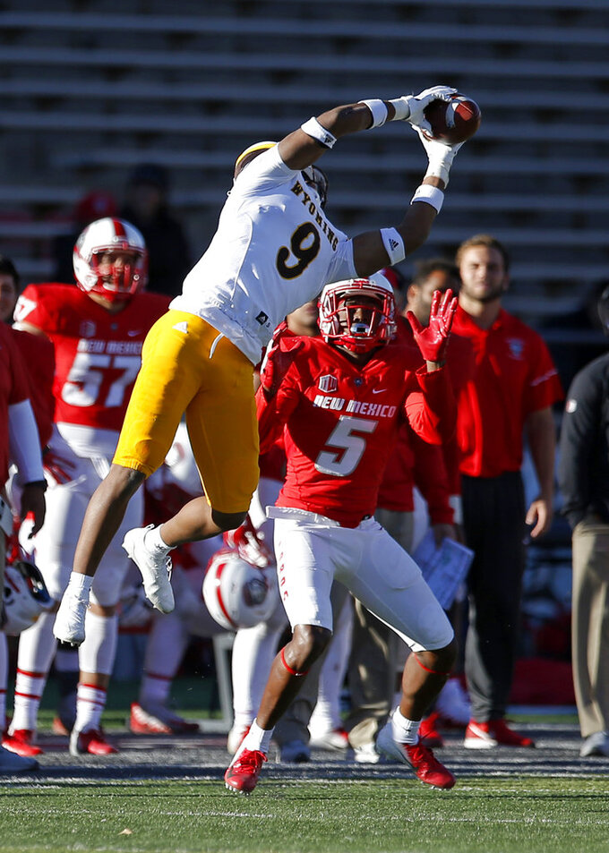 Wyoming linebacker Tyler Hall (9) intercepts a pass intended for New Mexico wide receiver Patrick Reed (5) during the second half of an NCAA college football game in Albuquerque, N.M., Saturday, Nov. 24, 2018. Wyoming won 31-3. (AP Photo/Andres Leighton)