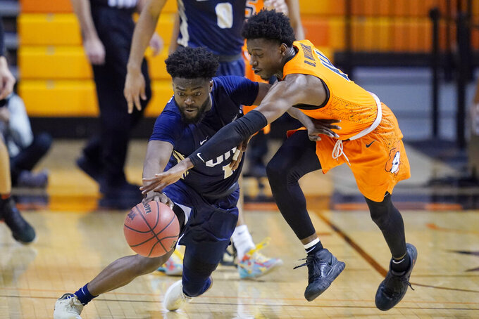 Oral Roberts guard RJ Glasper, left, and Oklahoma State guard Bryce Williams reach for the ball during the second half of an NCAA college basketball game Tuesday, Dec. 8, 2020, in Stillwater, Okla. (AP Photo/Sue Ogrocki)