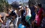 Volunteers distribute donations to victims of last week's tornado in El Roble, on the outskirts of Havana, Cuba, Wednesday, Feb. 6, 2019. Private aid started almost immediately after the Category F4 tornado struck on the night of Jan. 27 with winds of roughly 186 miles per hour (300 kph), damaging 3,800 homes and causing 372 total collapses.  (AP Photo/Ramon Espinosa)