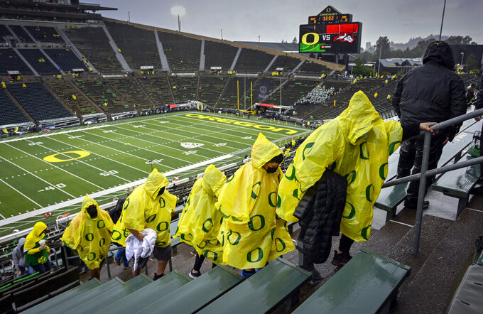 Oregon fans head to cover in Autzen Stadium due to a passing thunderstorm before Oregon plays Stony Brook in an NCAA college football game Saturday, Sept. 18, 2021, in Eugene, Ore. (AP Photo/Andy Nelson)