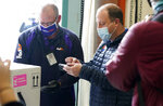 Colorado Governor Jared Polis signs for delivery of the state's first shipment of COVID-19 vaccine at the laboratory for the Colorado Department of Public Health and Environment, early Monday, Dec. 14, 2020, in Denver. (AP Photo/David Zalubowski)