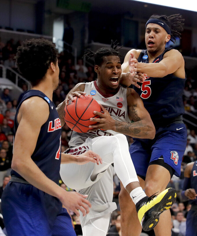 Virginia Tech guard Ahmed Hill, middle, drives to the basket between Liberty guard Darius McGhee, left, and forward Keenan Gumbs during the second half of a second-round game in the NCAA men's college basketball tournament Sunday, March 24, 2019, in San Jose, Calif. (AP Photo/Jeff Chiu)
