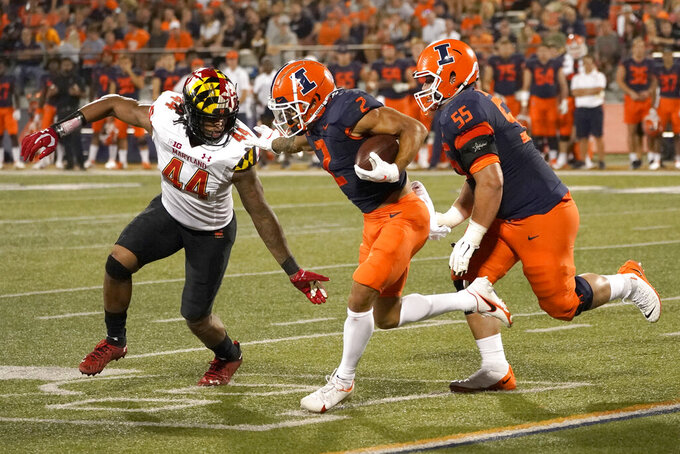 Illinois running back Chase Brown, center, stiff-arms Maryland linebacker Branden Jennings (44) as offensive lineman Blake Jeresaty comes up to make a block during the first half of an NCAA college football game Friday, Sept. 17, 2021, in Champaign, Ill. (AP Photo/Charles Rex Arbogast)