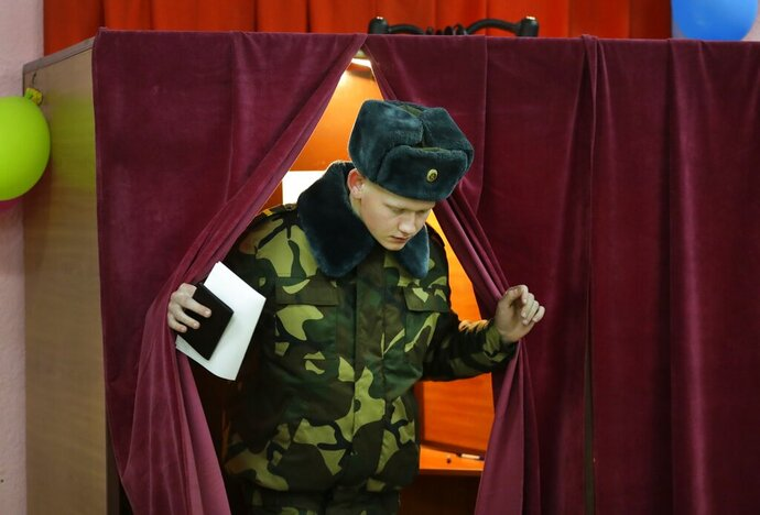 A Belarus' Army serviceman casts his ballot at a polling station during parliamentary elections, in Minsk, Belarus, Sunday, Nov. 17, 2019. (AP Photo/Sergei Grits)