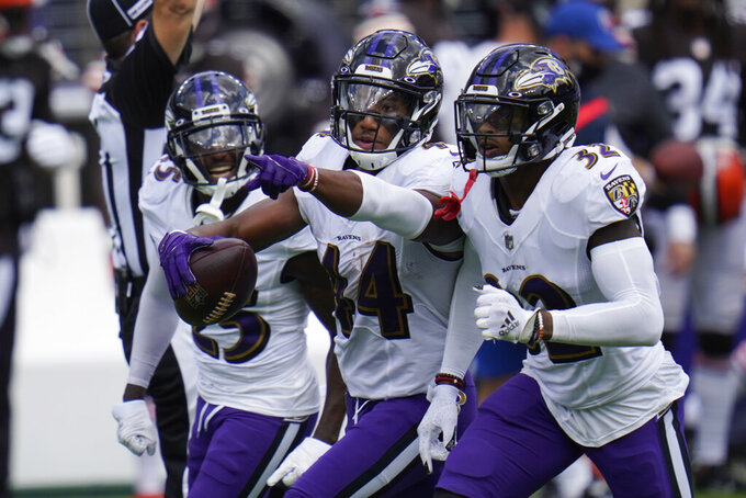 Baltimore Ravens cornerback Marlon Humphrey (44) celebrates after intercepting a pass, during an NFL football game against the Cleveland Browns, Sunday, Sept. 13, 2020, in Baltimore. To the right Baltimore Ravens safety DeShon Elliott (32) and cornerback Tavon Young (25), left. (AP Photo/Julio Cortez)