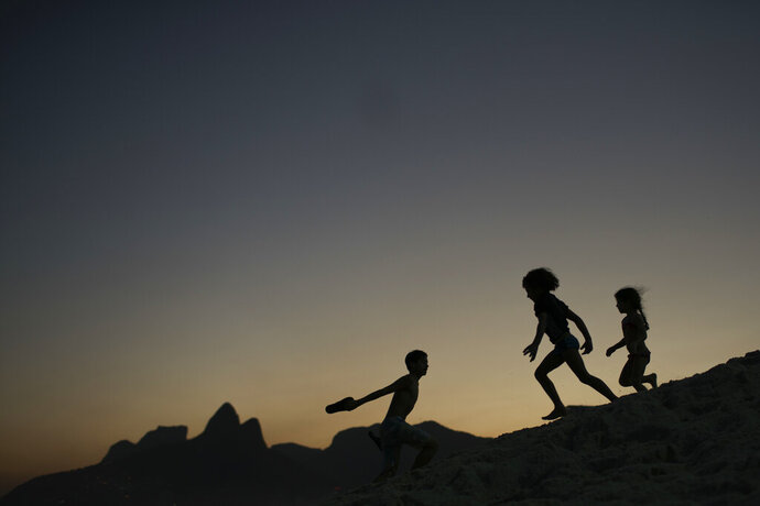 FILE - In this Aug. 1, 2016 file photo, children are silhouetted against the setting sun as they run on the sand at Ipanema beach in Rio de Janeiro, Brazil. Homeland Security investigators who uncover child exploitation initiated more than 4,000 cases around the world in 2019. Data obtained by The Associated Press shows the investigations resulted in thousands of arrests and the identification of more than 1,000 victims. On Thursday, Nov. 14, 2019, officials plan to unveil a new center based at Immigration and Customs Enforcement's headquarters in Washington tasked with alerting other countries when U.S. sex offenders are traveling there.  (AP Photo/Felipe Dana, File)
