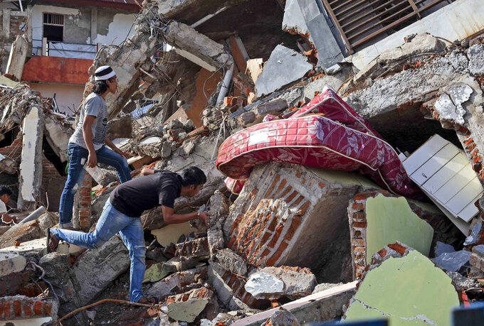 Residents inspect a building collapsed in Friday's earthquake in Mamuju, West Sulawesi, Indonesia, Monday, Jan. 18, 2021. Aid was reaching the thousands of people left homeless and struggling after an earthquake that killed a number of people in the province where rescuers intensified their work Monday to find those buried in the rubble. (AP Photo/Yusuf Wahil)