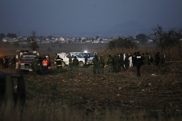 FILE - In this Dec. 24, 2018, file photo, emergency rescue personnel, the army and the police arrive work at the scene of a helicopter crash near Puebla City, Mexico. Four people have been arrested in connection with the crash that killed a central Mexican governor and her husband — who had preceded her as governor — authorities said Friday, Dec. 25, 2020. The Agusta 109 helicopter crashed in flames 10 minutes after takeoff on Dec. 24 that year while carrying newly installed Puebla Gov. Martha Erika Alonso and her husband, former Gov. Rafael Moreno Valle, as well as three other people. (AP Photo/Pablo Spencer, File)