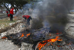 Firefighters burn debris during a cleanup at a tsunami-ravaged area in Palu, Central Sulawesi, Indonesia, Thursday, Oct. 11, 2018. A 7.5 magnitude earthquake rocked Central Sulawesi province on Sept. 28, triggering a tsunami and mudslides that killed a large number of people and displaced tens of thousands of others. (AP Photo/Dita Alangkara)
