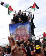 Protestors wave Palestinian flags during a rally supporting Palestinian President Mahmoud Abbas, shown in banner, and against the Mideast plan announced by U.S. President Donald Trump, at the Unknown Soldier Square in Gaza City, Tuesday, Feb. 11, 2020. (AP Photo/Adel Hana)