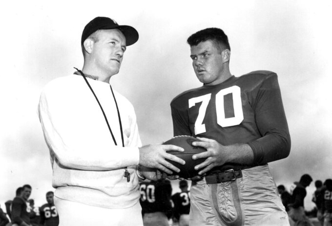 FILE- In this September 1958 file photo, Notre Dame football coach Terry Brennan, left, talks with tackle Bronko Nagurski Jr. during practice in South Bend, Ind. Brennan, a star halfback on three unbeaten Notre Dame teams who was hailed as a wunderkind when he succeeded Irish coaching great Frank Leahy at just 25 years old, has died. He was 93. The school announced his death Wednesday, Sept 8, 2021. (AP Photo, File)
