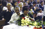 A supporter of Peru's late President Alan Garcia puts a flower on his coffin on the second day of his wake at his party's headquarters in Lima, Peru, Thursday, April 18, 2019. Garcia shot himself in the head and died Wednesday as officers waited to arrest him in a massive graft probe that has put the country's most prominent politicians behind bars and provoked a reckoning over corruption. (AP Photo/Martin Mejia)