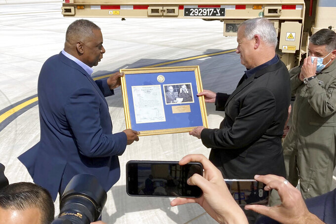 U.S. Defense Secretary Lloyd Austin, left, presents Israeli Defense Minister Benny Gantz, right, with a framed copy of a formerly Top Secret memo regarding U.S. consideration of granting official recognition of the state of Israel shortly after its creation in 1948, at Nevatim Israeli Air Force Base, Monday, April 12, 2021 in Israel. The inset photo on right shows President Truman and Secretary of State George Marshall. (AP Photo/Robert Burns)