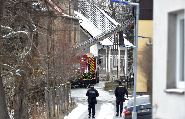Firefighters stand in front of a house, where eight people with mental and combined impairment were died and another three were seriously injured in the fire on Sunday, Jan. 19, 2020, in Vejprty, Czech Republic. (Slavomir Kubes/CTK via AP) ** SLOVAKIA OUT **