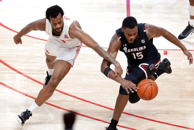 Houston forward Justin Gorham, left, fouls South Carolina forward Wildens Leveque while reaching for the ball during the second half of an NCAA college basketball game Saturday, Dec. 5, 2020, in Houston. (AP Photo/Michael Wyke)