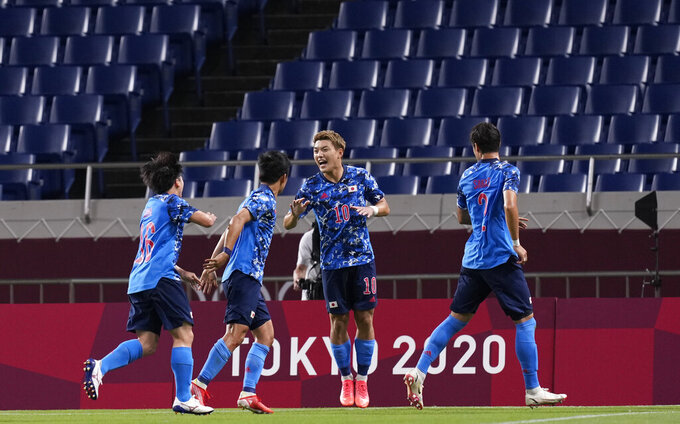 Japan's Ritsu Doan, center, celebrates with teammates after scoring a goal during a men's soccer match against Mexico at the 2020 Summer Olympics, Sunday, July 25, 2021, in Saitama, Japan. (AP Photo/Martin Mejia)