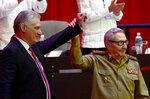 Raul Castro, right, raises the hand of Cuban President Miguel Diaz-Canel after Diaz-Canel was elected First Secretary of the Communist Party at the closing session of Cuban Communist Party's  8th Congress at the Convention Palace in Havana, Cuba, Monday, April 19, 2021. As Cuban President and the Communist Party leader, he replaces his mentor Raul Castro, sealing a political dynasty that had held power since the 1959 revolution. (Ariel Ley Royero/ACN via AP)