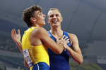 Armand Duplantis, left, of Sweden, and Sam Kendricks, right, of the United States, congratulate one another after the the men's pole vault final at the World Athletics Championships in Doha, Qatar, Tuesday, Oct. 1, 2019. (AP Photo/Hassan Ammar)