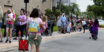 Parents and kids wait in line for close to an hour at Coral Square mall in Coral Springs, Fla., for the Build-A-Bear Workshop Pay Your Age day event Thursday, July 12, 2018. An offer allowed customers to purchase a bear and pay their current age with a cap at $29, which was also available at its United Kingdom stores. The chain known for its customizable teddy bears and other stuffed toys couldn't handle the crowds Thursday and had to turn shoppers away. (Carline Jean/South Florida Sun-Sentinel via AP)