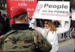 A protester holds a placard denouncing the government in front of soldiers during a protest against a parliament session to vote of confidence for the new government, in downtown Beirut, Lebanon, Tuesday, Feb. 11, 2020. (AP Photo/Hussein Malla)