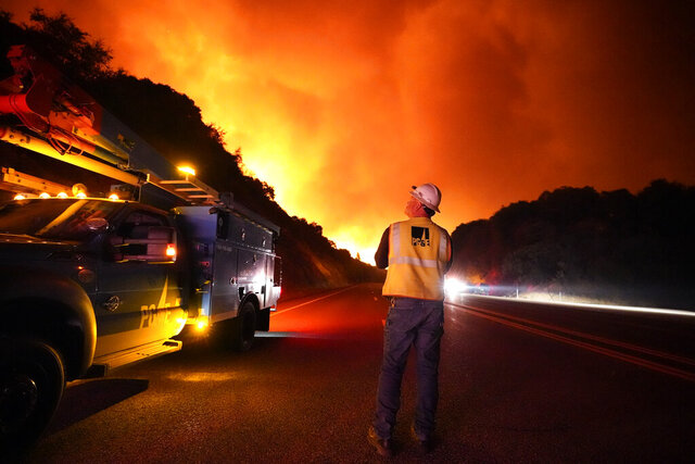 FILE - In this Tuesday, Sept. 8, 2020 file photo, A Pacific Gas and Electric worker looks up at the advancing Creek Fire along Highway 168 near Alder Springs, Calif. Pacific Gas & Electric will cut power to over 1 million people on Sunday to prevent the chance of sparking wildfires as extreme fire weather returns to the region, the utility announced Friday. Oct. 23, 2020.  (AP Photo/Marcio Jose Sanchez, File)