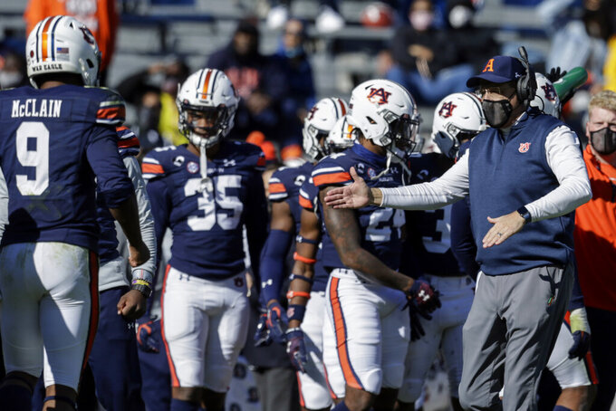 Auburn head coach Gus Malzahn reacts with players after a stop against Texas A&M during the first half of an NCAA college football game on Saturday, Dec. 5, 2020, in Auburn, Ala. (AP Photo/Butch Dill)