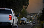 In this Thursday, Sept. 13, 2018, photo vehicles evacuate from Elk Ridge, Utah during a mandatory evacuation a wildfire moves toward homes. A fast-moving Utah wildfire fanned by high-winds has more than doubled in size as it burns through dry terrain and forces evacuations of hundreds of homes, the U.S. Forest Service said Friday. (Isaac Hale/The Daily Herald via AP)