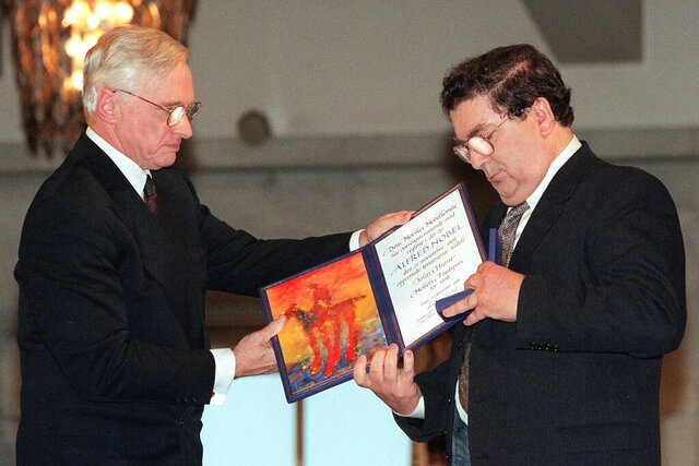 FILE - In this Dec. 10, 1998 file photo, John Hume, right, looks at the Nobel Peace Prize diploma which he received from Francis Sejersted, left, chairman of the Norwegian Nobel Peace Prize Committee during the award ceremony in Oslo Town Hall. The family of politician John Hume, who won Nobel Peace Prize for work to end violence in Northern Ireland, says he has died. He was 83. The Catholic leader of the moderate Social Democratic and Labour Party , Hume was regarded by many as the principal architect behind the peace agreement. (AP Photo/Bjoern Sigurdsoen/NTB/POOL)