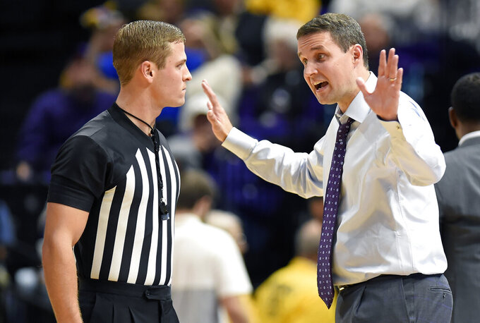LSU coach Will Wade, right, talks with an official during the first half of the team's NCAA college basketball game against UMBC, Tuesday, Nov. 19, 2019, in Baton Rouge, La. (AP Photo/Bill Feig)