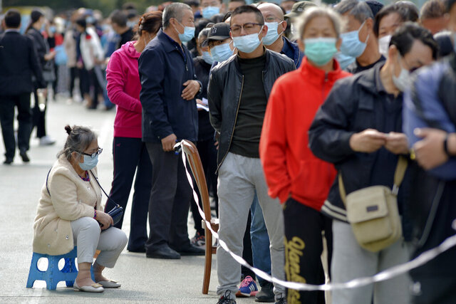 A woman wearing a face mask to help curb the spread of the coronavirus sits on a stool as masked residents line up for the COVID-19 test near the residential area in Qingdao in east China's Shandong province, Monday, Oct. 12, 2020. China's government says all 9 million people in the eastern city of Qingdao will be tested for the coronavirus this week after nine cases linked to a hospital were found. The announcement Monday broke a string of weeks without any locally transmitted infections reported in China. (Chinatopix via AP)