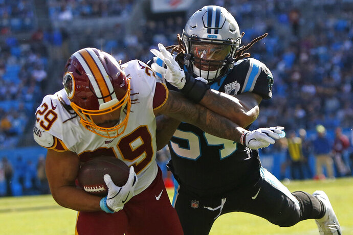 Carolina Panthers outside linebacker Shaq Thompson tackles Washington Redskins running back Derrius Guice (29) during the first half of an NFL football game in Charlotte, N.C., Sunday, Dec. 1, 2019. (AP Photo/Brian Blanco)