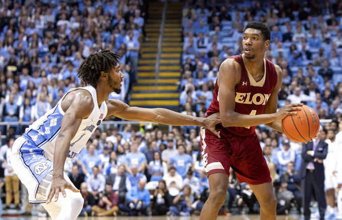 Elon's Marcus Sheffield II, right, handles the ball as North Carolina's Leaky Black (1) defends during the second half of an NCAA college basketball game in Chapel Hill, N.C., Wednesday, Nov. 20, 2019. (AP Photo/Ben McKeown)