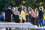 People gather at the scene after a Premiere #1 Limousinebus crashed into a wooded area off I-81 in Frailey Township, Pa., on Sunday, Sept. 19, 2021. The bus was traveling on I-81 south and came off the Hegins exit ramp, crossing through the divider on Rt. 25 and crashing into a wooded area off Rt. 25 where it came to a stop. (Jacqueline Dormer/Republican-Herald via AP)