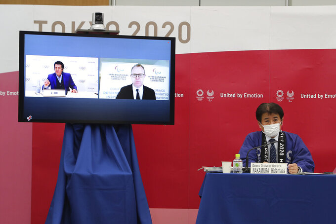 """Hidemasa Nakamura, right, games delivery officer for the Tokyo Organizing Committee of the Olympic and Paralympic Games (Tokyo 2020), joins other representatives from the International Olympic Committee (IOC) and the International Paralympic Committee (IPC) at a Joint press briefing in Tokyo on Wednesday, Feb. 3, 2021. Tokyo 2020, IOC and IPC announced Wednesday they jointly developed and published the first version of """"The Playbooks,"""" which contains advice from international and Japanese health experts for COVID-19 countermeasures as well as the guidelines and rules that each games stakeholder will need to observe in order to play their part in ensuing a safe and secure games. (Du Xiaoyi/Pool Photo via AP)"""