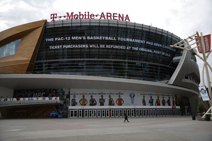 A sign at T-Mobile Arena advertises the cancellation of the Pac-12 men's basketball tournament amid coronavirus fears Thursday, March 12, 2020, in Las Vegas. The vast majority of people recover from the new virus. According to the World Health Organization, people with mild illness recover in about two weeks, while those with more severe illness may take three to six weeks to recover. (AP Photo/John Locher)
