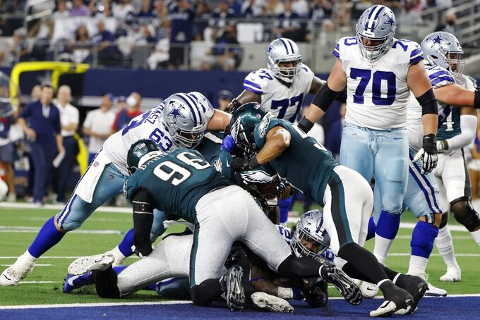 Dallas Cowboys running back Ezekiel Elliott, bottom of pile looking forward, reaches the end zone for a touchdown as Philadelphia Eagles' Derek Barnett (96) and others defend in the first half of an NFL football game in Arlington, Texas, Monday, Sept. 27, 2021. (AP Photo/Michael Ainsworth)